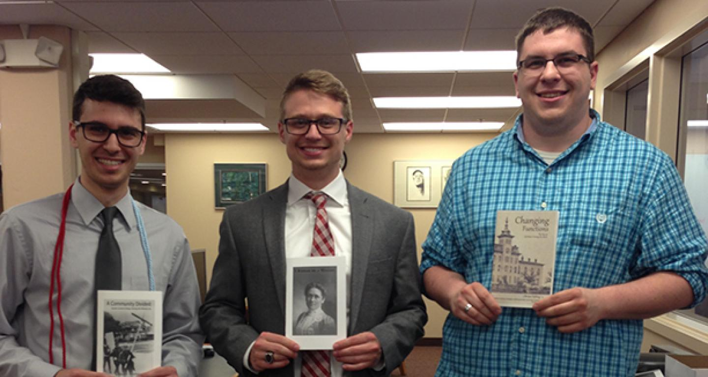 Three young men holding up their Undergraduate Archives Research Publications