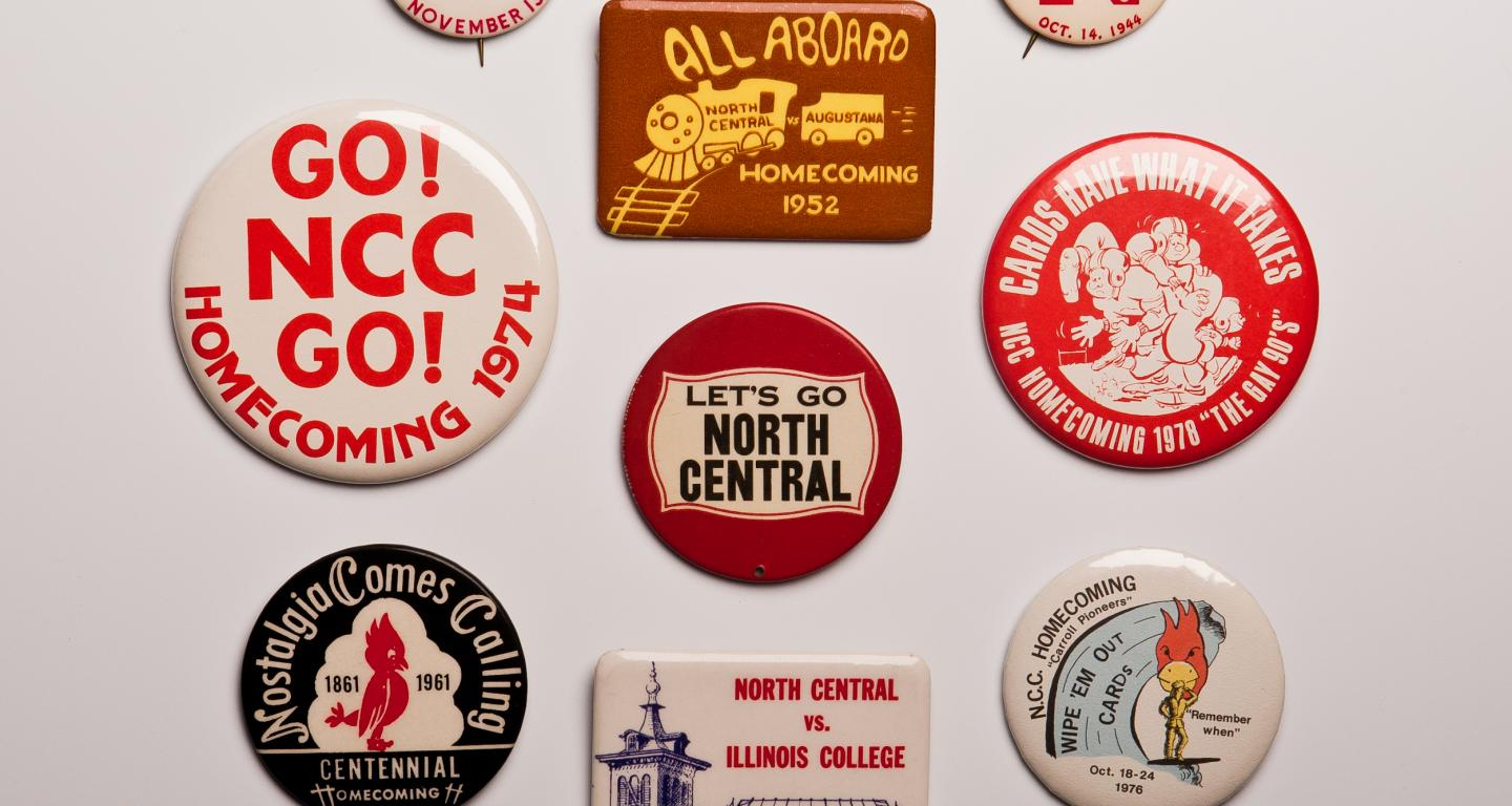 A variety of metal buttons from North Central College homecoming games scattered on a white background