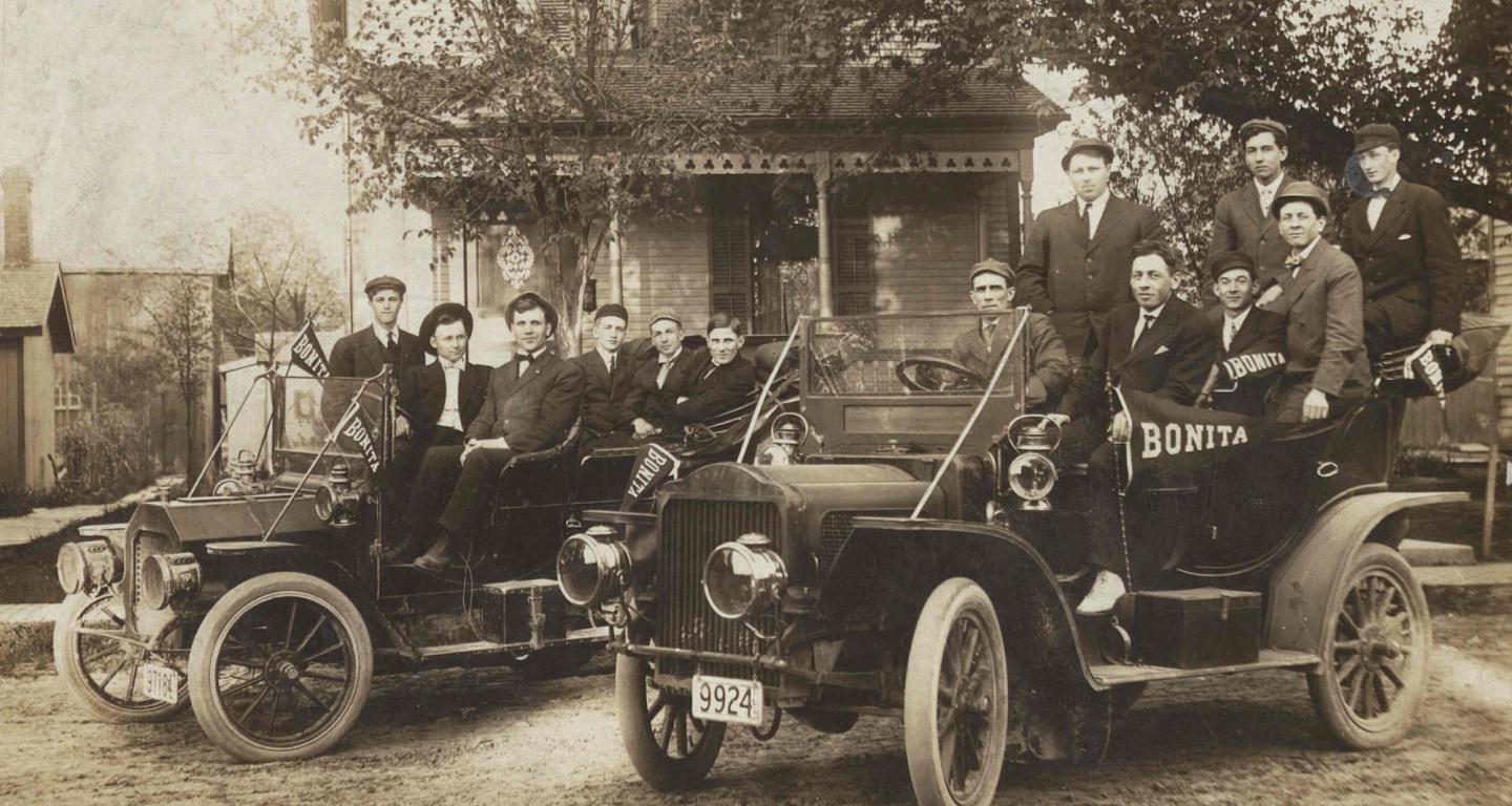 Several young people sit in two 1930s automobiles in front of a house
